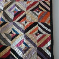 Quilt made with various widths of fabric strips.